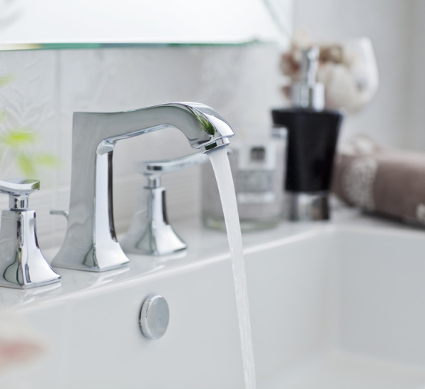 An image showing a white bathroom sink, fitted by EGP Plumbers, with a running tap.