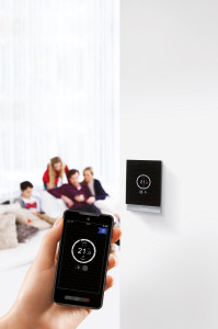 An image showing someone controlling their home heating system with an app.