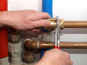 An image showing an EGP Plumbers central heating engineer fixing a home heating system.