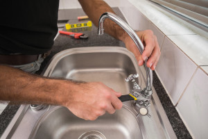 An image of an emergency plumber fixing a sink tap.
