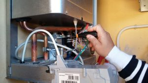 An image of a an engineer fixing common boiler problems.