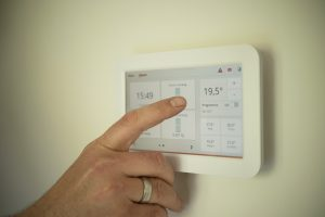 An image of a man controlling the temperature of his home using a digital display system